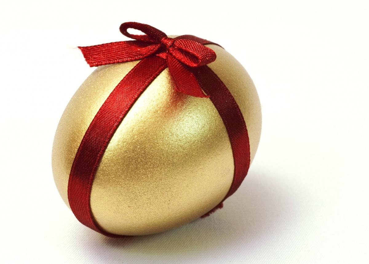 uovo di pasqua dorato con nastro rosso