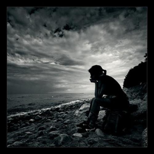 donna pensierosa e triste in riva al mare con nuvole in bianco e nero