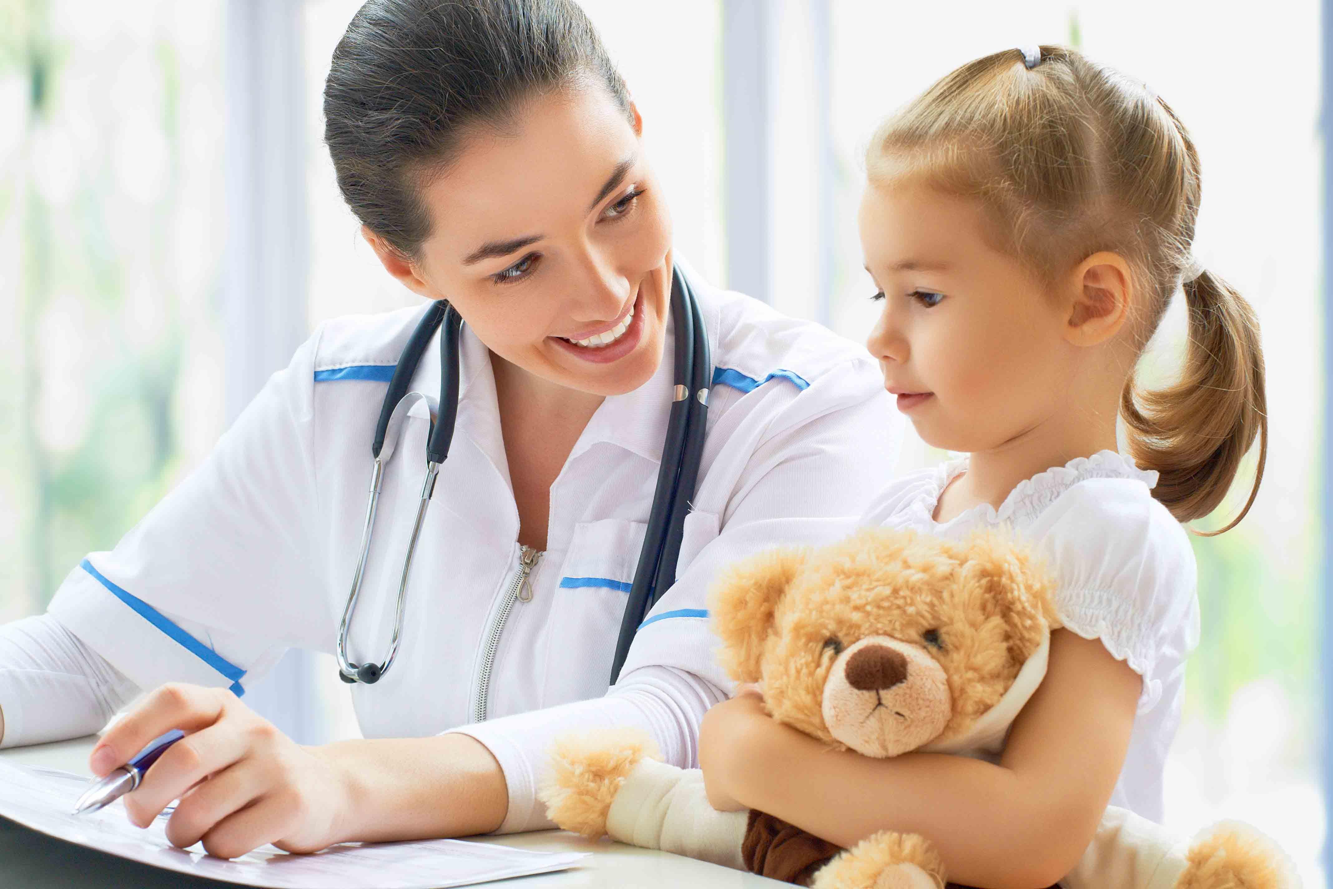 pediatra donna parla con bambina con orsacchiotto